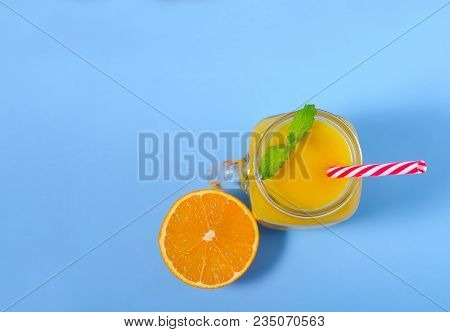 Yellow Smoothie In Mason Jar Glass With Mint And Orange. Above View On Blue Table. Healthy Food. Abo