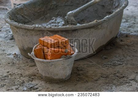 Red Brick In Plastic Bucket On Construction Wall Site