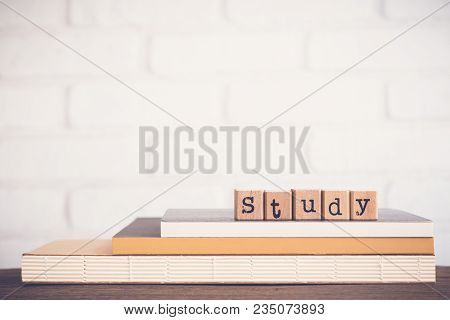 The Word Study, Alphabet On Wooden Rubber Stamps On Top Of Books And Table. Bricks Background, Blank