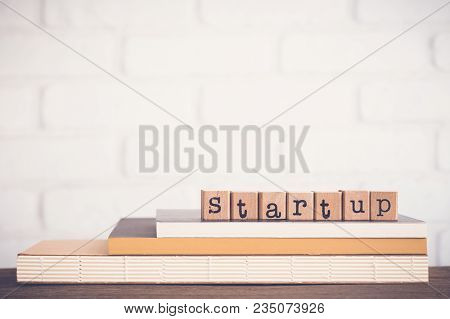 The Word Startup, Alphabet On Wooden Rubber Stamps On Top Of Books And Table.  Background Copy Space
