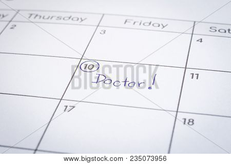 Closeup On Calendar Page, Focus On Blue Handwriting The Worddoctor Written On Timetable Date 10th W