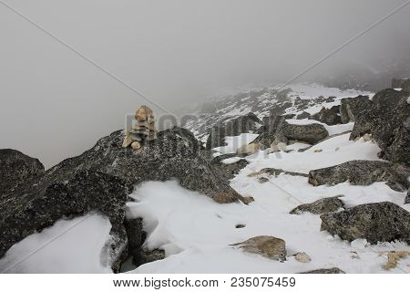Mountain Ridge On A Fogy Spring Day. Stone Cairn.