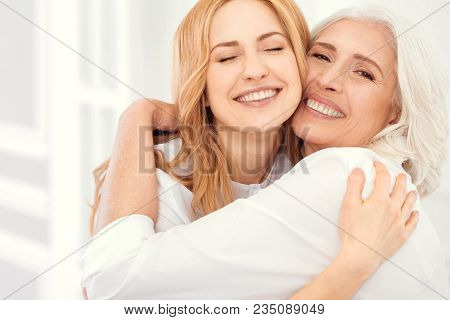 Happiness Is Homemade. Sunshiny Mature Daughter And Her Elderly Mom Grinning Broadly Into The Camera