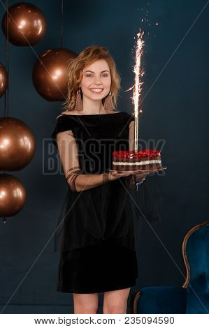 Young Girl Holding Birthday Cake With Burning Firework On Black Wall Background.