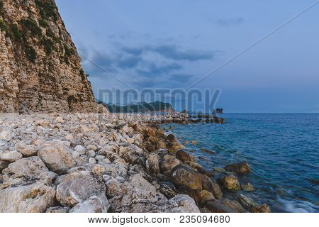 Wild Shore Scene With Sea Surf, Cloudy Sky, Stones And Rocks. Montenegro Landscape With Pebble Beach