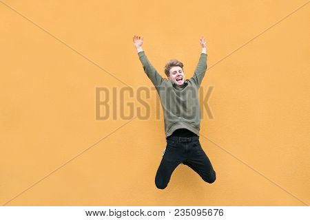 A Young Man In Casual Clothes Jumps On The Background Of An Orange Wall. Emotional Jump Of A Happy M