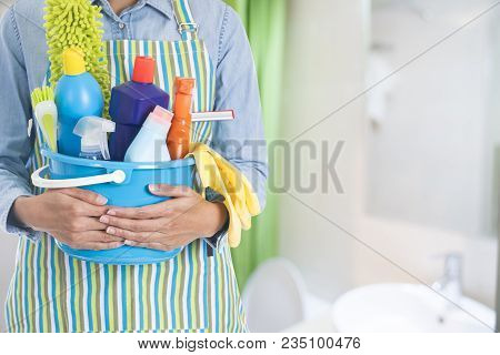 Woman With Cleaning Equipment Ready To Clean House On Bathroom Background