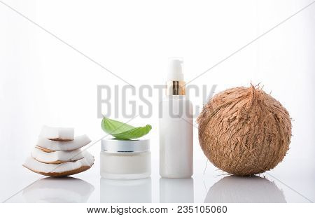 Homemade Cosmetic Coconut Products With Coconut On White Background. Lotion Cream With Coconut Stack