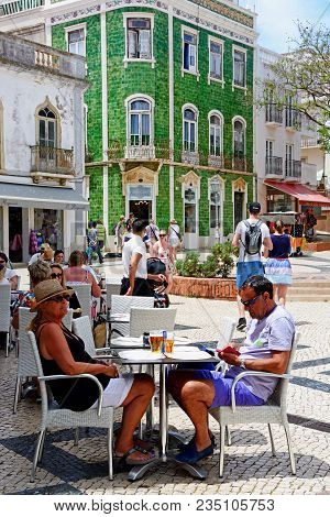 Lagos, Portugal - June 9, 2017 - Tourists Relaxing At Pavement Cafes In The Praca Luis De Camoes Wit