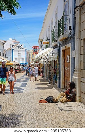 Lagos, Portugal - June 9, 2017 - Performer Sitting On The Cobbled Shopping Street Playing His Guitar