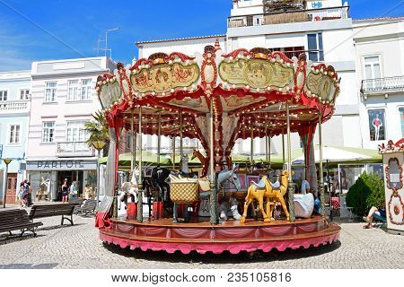 Lagos, Portugal - June 9, 2017 - Animal Carousel Fairground Ride Along The Rua Porta De Portugal Wit