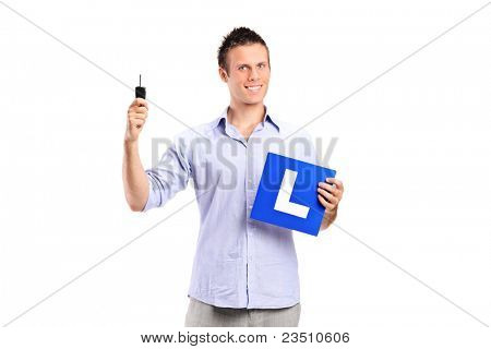 Happy man holding a car key and L plate isolated against white background