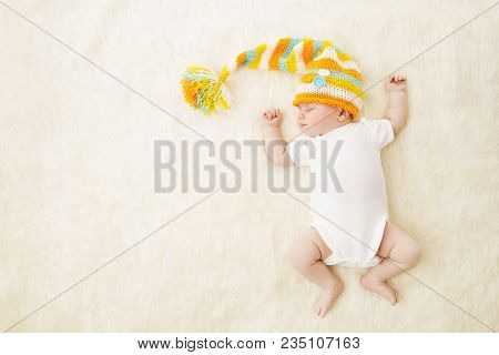 Baby Sleep Colorful Hat, Newborn Child In Bodysuit Sleeping On Carpet Background, Infant Kid In Bed