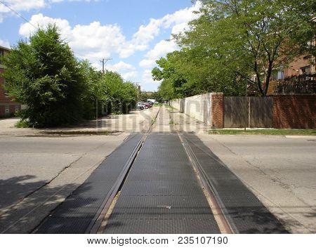 Looking Straight Down A Pair Of Railroad Tracks Running Through A Urban Neighborhood In Summer