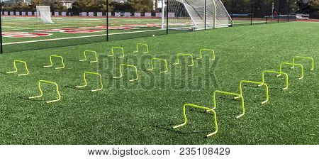 12 Inch Banana Hurdles Set Up On A Green Turf Field For Speed Training At Track And Field Practice.