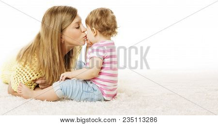 Mother Kiss Her Daughter, Infant Kid Kissing Mom, Happy Baby Sitting In Home On White Carpet