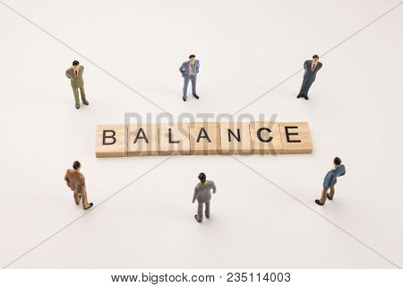 Miniature Figures Businessman : Meeting On Balance Word By Wooden Block Word On White Paper Backgrou