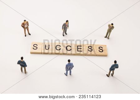 Miniature Figures Businessman : Meeting On Success Word By Wooden Block Word On White Paper Backgrou