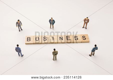 Miniature Figures Businessman : Meeting On Business Word By Wooden Block Word On White Paper Backgro