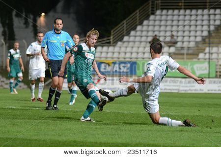 KAPOSVAR, HUNGARY - SEPTEMBER 10: Serghei Alexeev (in white) in action at a Hungarian National Championship soccer game - Kaposvar (white) vs Gyor (green) on September 10, 2011 in Kaposvar, Hungary.