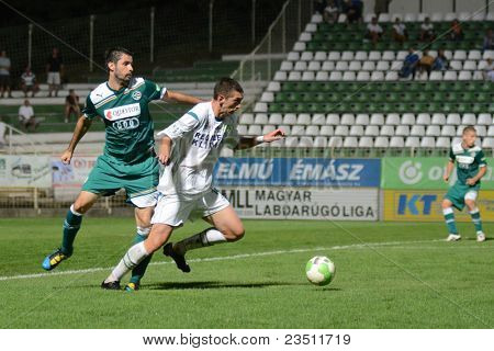 KAPOSVAR, HUNGARY - SEPTEMBER 10: Serghei Alexeev (white 14) in action at a Hungarian National Championship soccer game - Kaposvar (white) vs Gyor (green) on September 10, 2011 in Kaposvar, Hungary.
