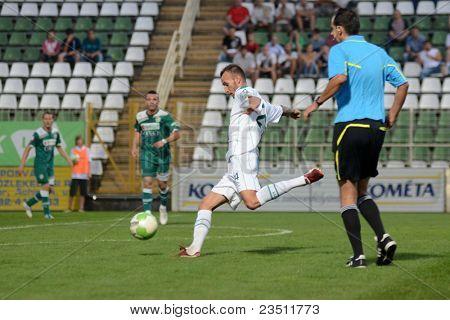 KAPOSVAR, HUNGARY - SEPTEMBER 10: David Hegedus (in white) in action at a Hungarian National Championship soccer game - Kaposvar (white) vs Gyor (green) on September 10, 2011 in Kaposvar, Hungary.