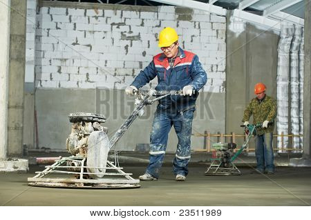 Worker trowelling and finishing of concrete by special construction equipment