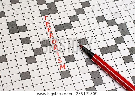 Terrorism. Text In Crossword. Red Letters. Close-up