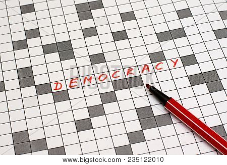 Democracy. Text In Crossword. Red Letters. Close-up
