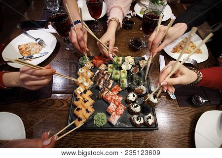 A Set Of Sushi Rolls On A Table In A Restaurant. A Party Of Friends Eating Sushi Rolls Using Bamboo