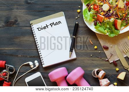 Top View On Wooden Table With Salad, Dumbbells, Measure Tape, Smartphone And  Notebook With Diet Pla
