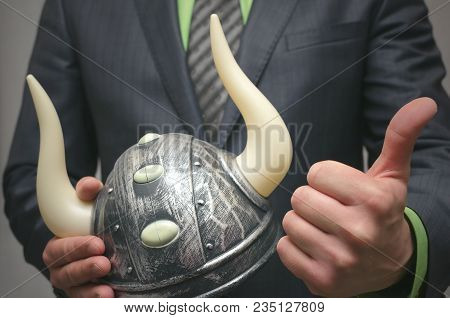 Bull stock broker. Bull market concept. Agressive business strategy. Business man holding a toy viking helmet in hands. Boosting price game on the stock exchange. poster