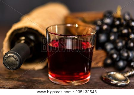 Close Up Glass Of Red Wine With Bottle And Fresh Grapes. Selective Focus