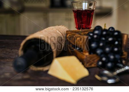 Close Up Glass Of Red Wine With Bottle, Cheese, Bottle Opener And Fresh Grapes. Selective Focus