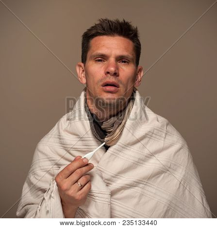 Concept Illness And Ill Health. Young Man Wrapped In A Blanket Holds A Thermometer During Illness An