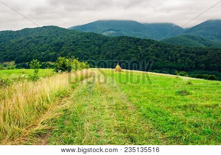 Path Down The Rural Field On Hillside. Lovely Countryside Scenery With Haystack And Forested Mountai