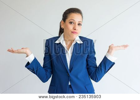 Careless Business Woman Shrugging Shoulders. Portrait Of Puzzled Young Caucasian Woman In Blue Forma