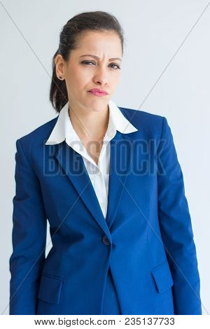 Portrait Of Frowning And Suspicious Business Woman. Pensive Young Caucasian Woman In Formal Wear Loo