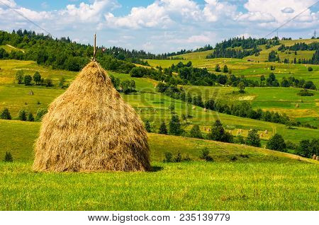 Haystack On The Grassy Field. Beautiful Summer Countryside Of Mountainous Area
