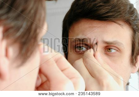 Young Man Plucking His Eyebrows With Tweezers. Styling Eyebrows