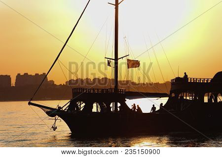 Silhouette Of A Beautiful Ship With Balks, Lowered Sails, Waving Flags And A Raised Anchor With Many