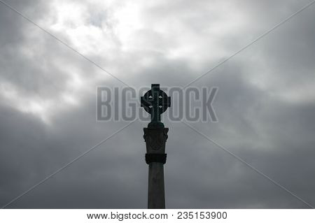 Celtic Stone Cross Silhouetted Against A Soft Grey Cloudy Sky