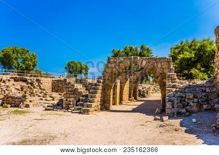 Israel. Sunny spring day. Excursion to the Archaeological Park of the Roman Empire in ancient Caesarea. The remains of the covered arcades. Concept of historical and ecological tourism