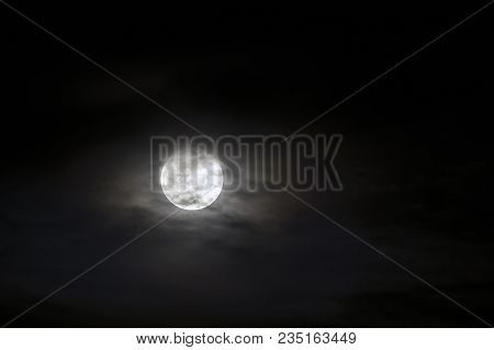 Big Silver Glowing Moon Close-up On Dark Blue Sky With Scattered Clouds.