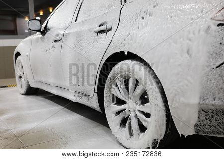 A car in foam during cleaning on a car wash