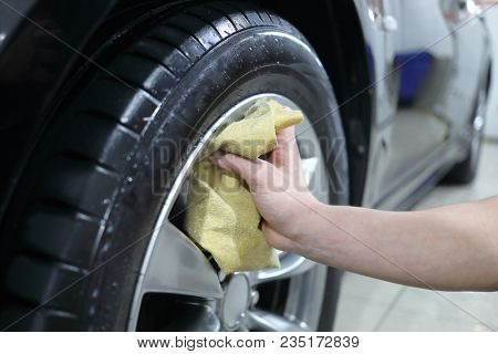 The washer of cars wipes a wheel of the car with a rag