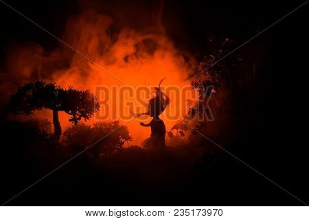 Horror Halloween Decorated Conceptual Image. Alone Girl With The Light In The Forest At Night. Silho