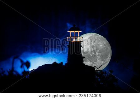 Lighthouse With Light Beam At Night With Fog. Old Lighthouse Standing On Mountain. Table Decoration.