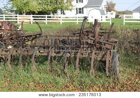 Rusted Farming Equipment In The Yard And The Weeds
