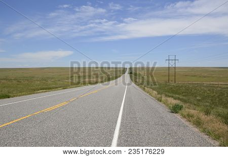 Paved Road In The Middle Of Nowhere On A Hot Summer Day In Open Farmland